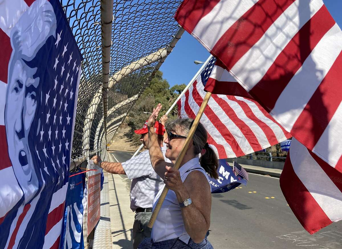 David Gaskell,53, and Chris Bratton, 65, wave flags in support of Donald Trump on an overpass above Highway 24 Monday