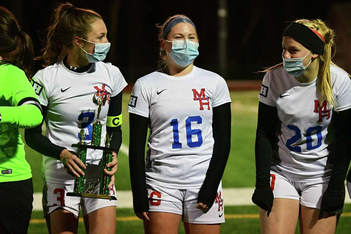 Maple Hill's Alayna Fletcher's eyes, #16, gives away her big smile under her face mask as the team celebrates defeating Greenville during the Patroon Conference girls' soccer title game on Monday, Nov. 2, 2020 in Craryville, N.Y. Fletcher scored the only goal of the game. (Lori Van Buren/Times Union)