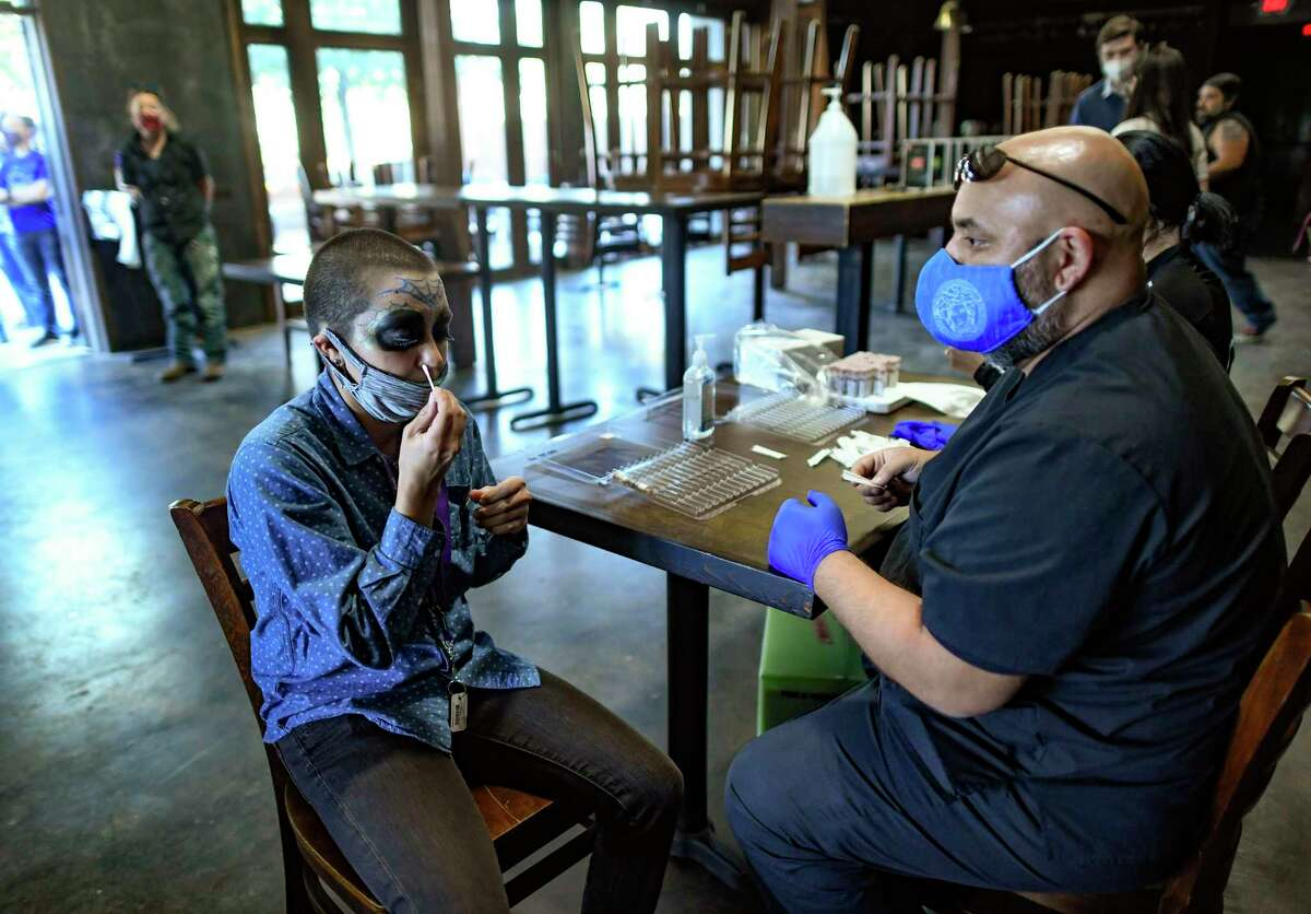 Sara Johnson swabs her nostrils for a COVID-19 test through Community Labs at The Hoppy Monk on Monday, Nov. 2, 2020.