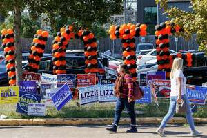 People walk past the Metropolitan Multi-Service Center during the last day of early voting Friday, Oct. 30, 2020, in Houston.