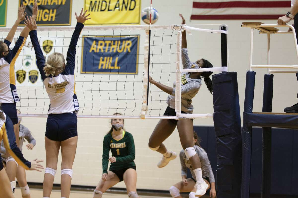Dow's Dez Okoro jumps to spike the ball during a match against Mount Pleasant Monday, Nov. 2, 2020 at Mount Pleasant High School. (Cody Scanlan/for the Daily News)