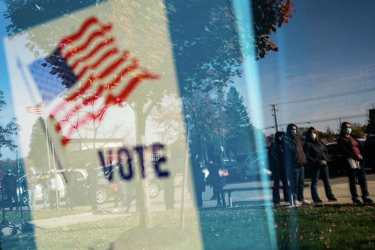 People wait in line to cast their absentee ballots in person at a senior center in Sterling Heights, Mich.