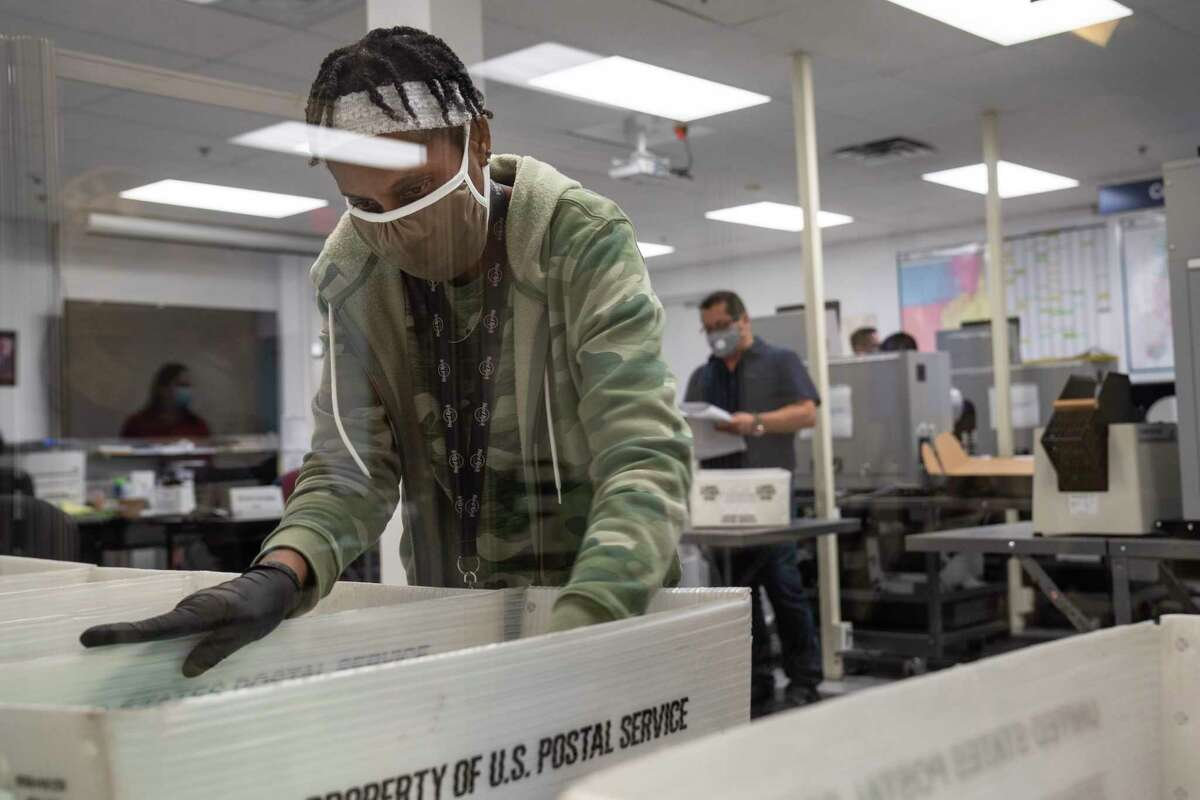 Employees count early and mail-in ballots at the Miami-Dade County Elections Department in Doral, Fla., on Friday.