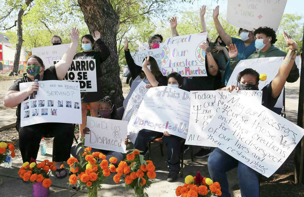 San Antonio Housing Authority residents raise their hands Monday as they protest a mixed- income apartment complex planned at the intersection of South Colorado and El Paso Street.