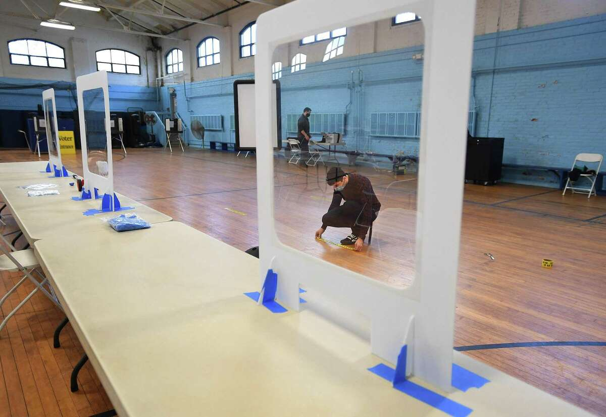 Republican Registrar of Voters David Papcin lays out social distancing tape in preparation for the 2020 election at the Ansonia Armory in Ansonia, Conn. on Monday, November 2, 2020.