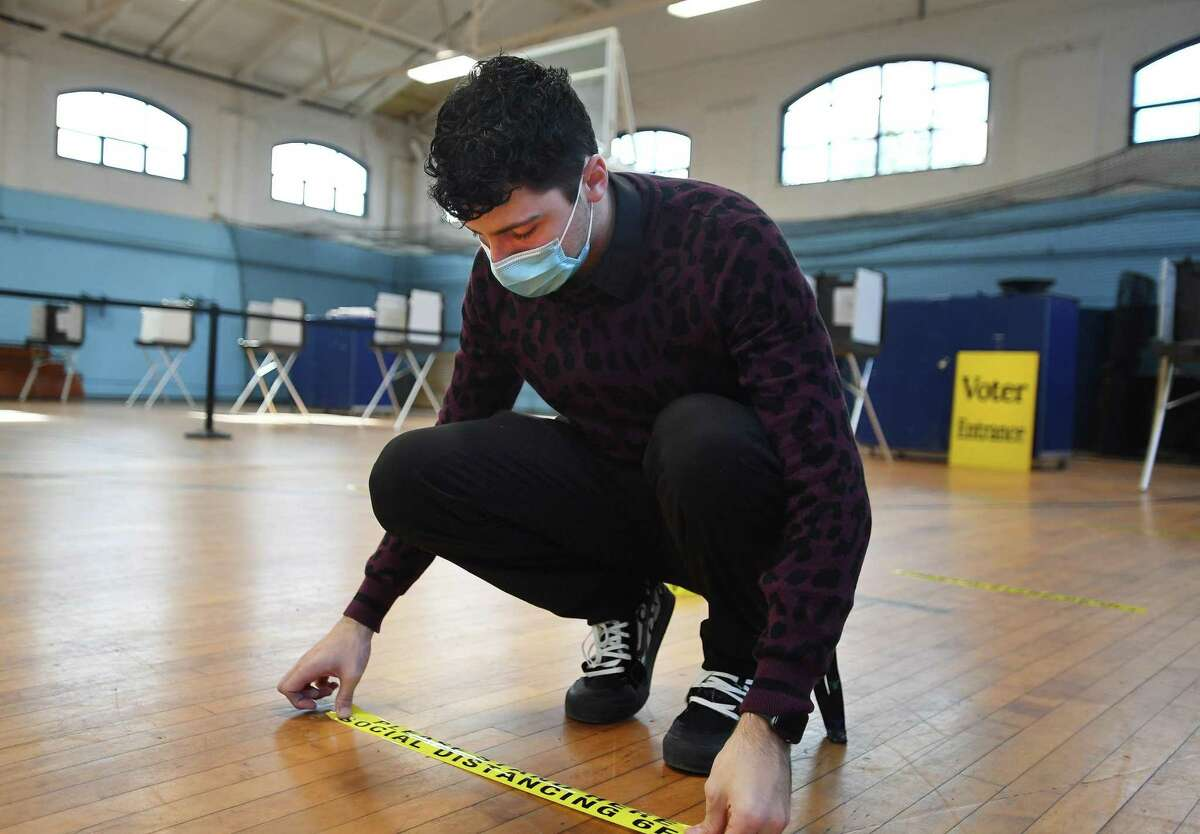 Republican Registrar of Voters David Papcin lays out social-distancing tape Monday in preparation for the 2020 election at the Ansonia Armory.