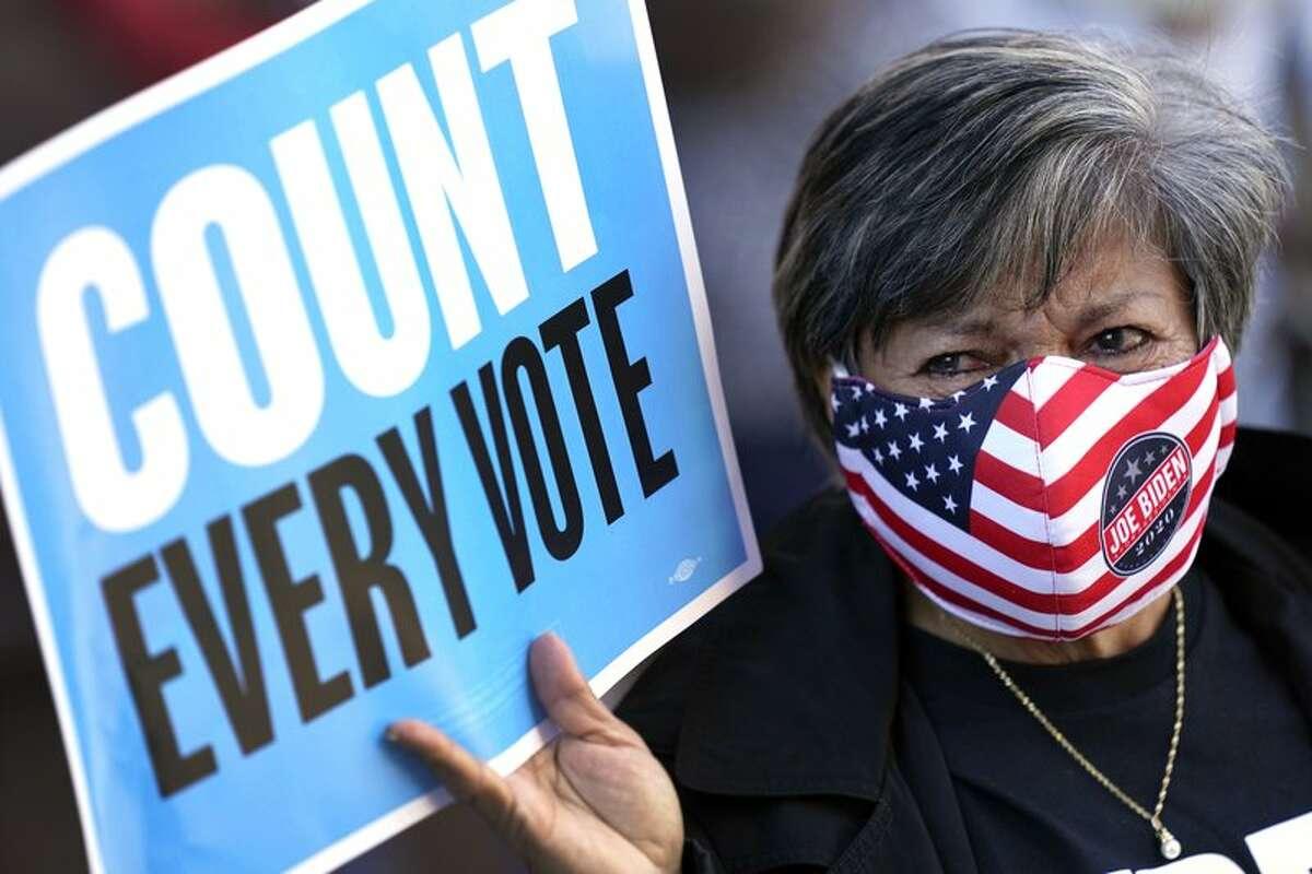 Una trabajadora electoral se une a una manifestación frente a un tribunal de Houston el lunes 2 de noviembre de 2020, previo a una audiencia que involucra votos emitidos desde vehículos en el condado de Harris.