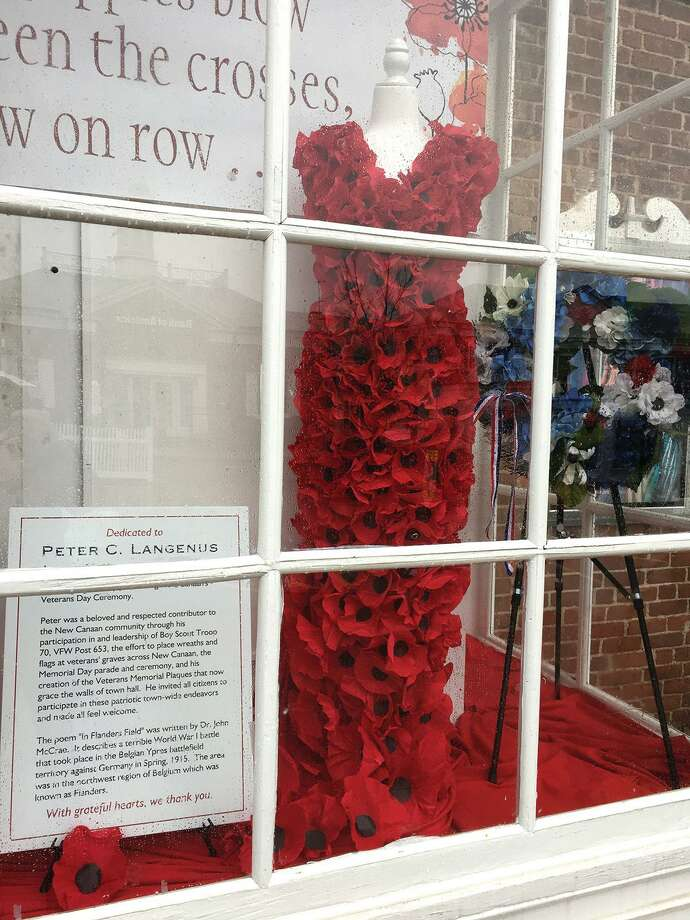Members of the Hannah Benedict Carter Chapter of the Daughters of the American Revolution fashioned a dress from crepe paper poppies for a display in the window of the New Canaan Playhouse on Elm Street, dedicated to the late Peter Langevin. Photo: Contributed Photo / DAR / New Canaan Advertiser Contributed