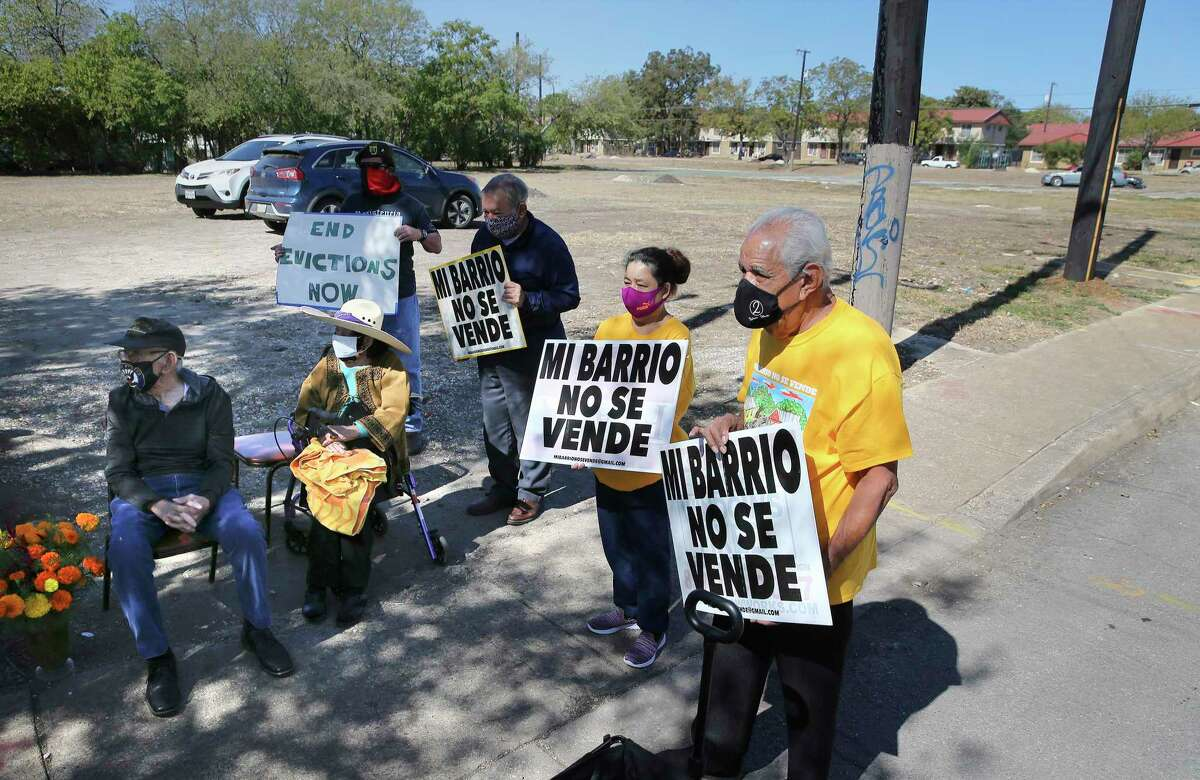 """People carry signs that, translated into English, say: """"My community is not for sale,"""" near property that San Antonio Housing Authority intends to turn into a mixed-income development. On Monday, Nov. 2, 2020, SAHA residents and others protested the development of the project called Legacy at Alazan."""