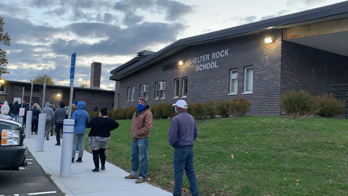 Voters get in line early at Shelter Rock School on Nov. 3, 2020. Shelter Rock School, Danbury The line at Shelter Rock School stretched from the back gym entrance, down the sidewalk in front of the school and to the sidewalk along the road, according to our breaking news reporter at the scene, Tara O'Neill.   One Danbury police cruiser was stationed outside the polling location. The parking lot was packed with new voters taking the places of other voters who already filed their ballots. Parked cars filled the street outside the school as the line of voters grew. Poll workers reminded voters to socially distance themselves and stay safe while in line.
