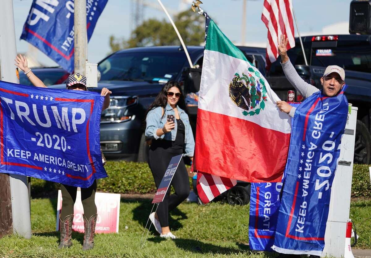 Jose Casares, right, and other Trump supporters wave flags across the street from the polling location the Metropolitan Multi-Services Center, 1475 West Gray St., on Election Day Tuesday, Nov. 3, 2020 in Houston.