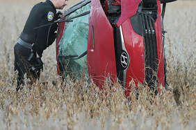 An Alton Police officer looks inside a red Hyundai early Tuesday morning as it lays on its side in a soybean field off Fosterburg Road south of Emma Kaus Lane in Alton. The body of a female occupant, who was apparently ejected, was found in the field about 40 feet away. The fatal accident apparently occured during the night but was not reported until around 6 a.m. Tuesday. Police and firefighters searched the bean field for any other occupants, but apparently found none. Fosterburg Road was closed to all traffic for an investigation for about four hours.