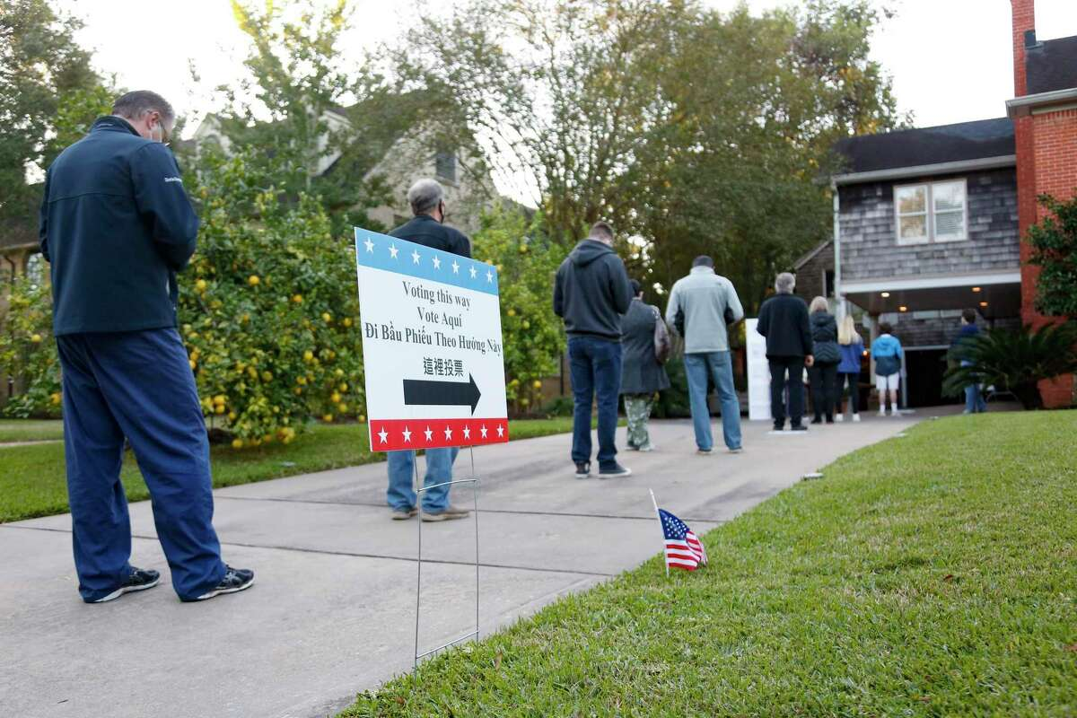 Voters line up in the driveway of Joanne Brodsky's home for voting in Houston on Tuesday, Nov. 3, 2020. Brodsky's garage is a polling station in Harris County.