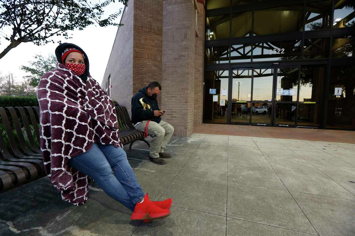 Natasha Butler attempted to stay warm after arriving at 5am to the Tom Reid Library to cast her vote Tuesday, Nov. 3, 2020, in Pearland. Butler's son, Jaedyn turned 18 on Sunday and she wanted to go to the polls with him.
