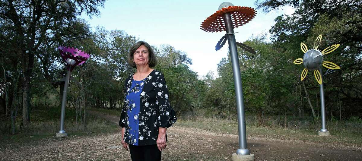 """Leticia Huerta poses by her art installation """"Bloom"""" at McAllister Park. The installation has been so popular with park-goers that the city has commissioned her to created more floral installations for parks across the city."""