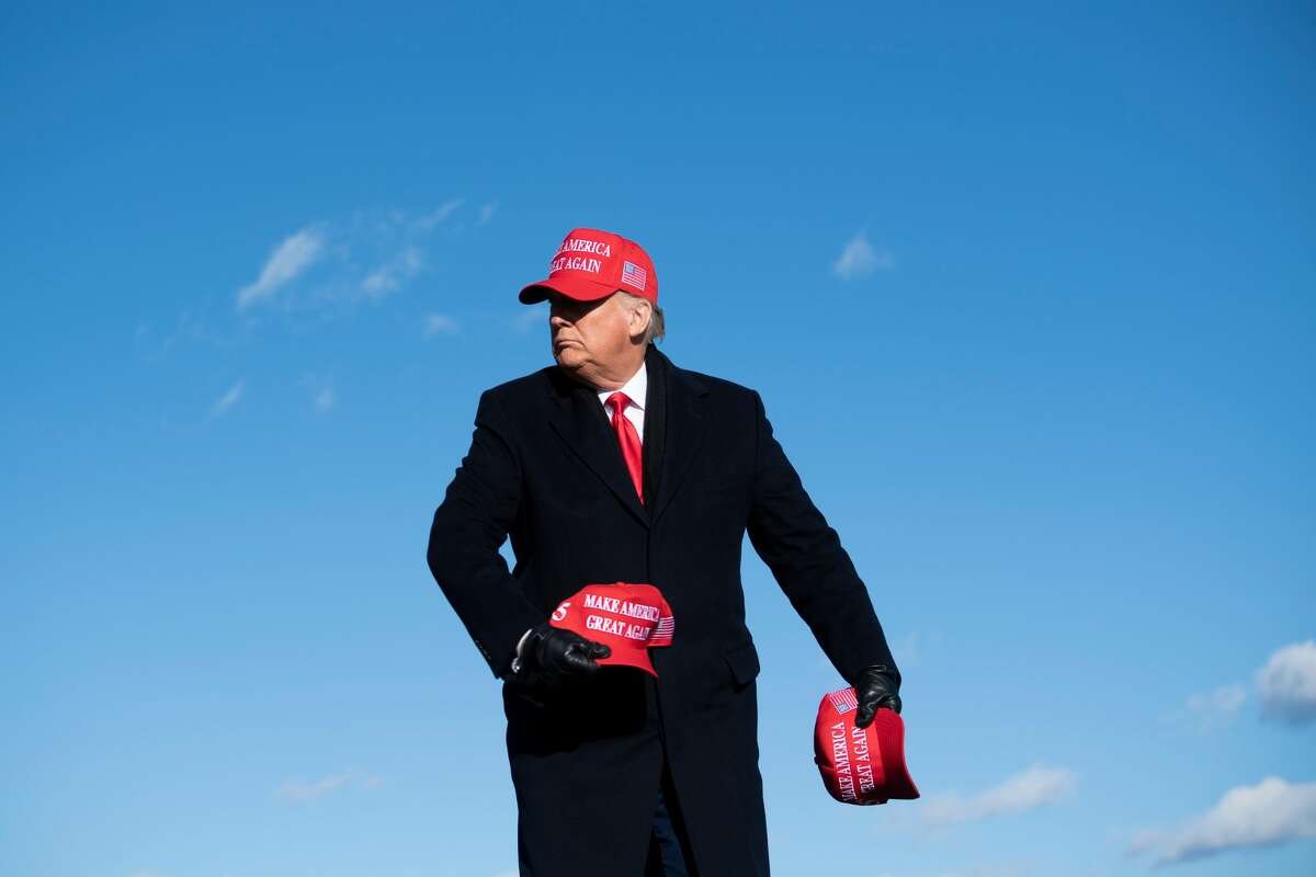 TOPSHOT - US President Donald Trump throws hats to supporters during a Make America Great Again rally at Wilkes-Barre Scranton International Airport November 2, 2020, in Avoca, Pennsylvania. - The US presidential campaign enters its final day Monday with a last-minute scramble for votes by Donald Trump and Joe Biden, drawing to a close an extraordinary race that has put a pandemic-stricken country on edge. (Photo by Brendan Smialowski / AFP) (Photo by BRENDAN SMIALOWSKI/AFP via Getty Images)