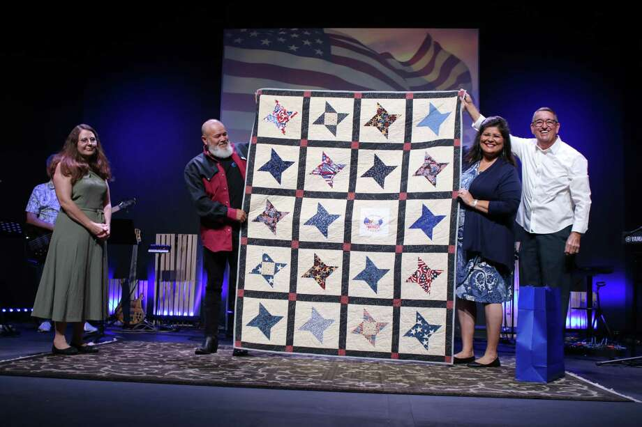 The Golden Needles Quilt Guild presents a handmade patriotic quilt to Ezequiel Tamarit, left, on Oct. 18 at Carbon Church in Conroe. Each year the guild presents quilts to veterans in the community. Pictured from left are Paula Tamarit, guild member Mary Olivarez and 2019 quilt recipient James Larry Ray. Photo: Courtesy Photo
