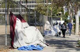 Pedestrians walk past a homeless encampment just outside Grand Park, Wednesday, Oct. 28, 2020, in Los Angeles. Los Angeles is again considering a proposal to greatly restrict where homeless people may camp in public places around Los Angeles - rules that opponents say would criminalize homelessness. (AP Photo/Chris Pizzello)