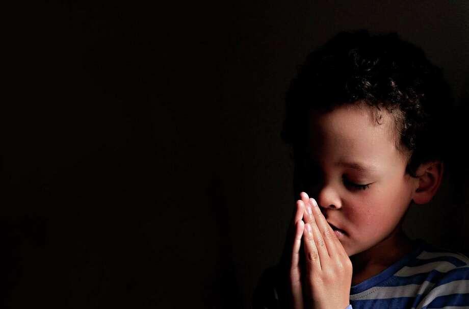A little boy praying to God. Photo: Dreamstime / (c) Derektenhue   Dreamstime.com