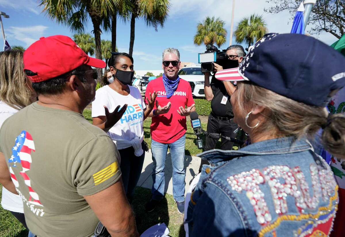 Laurie Robinson, a Biden supporter, second from left, has a friendly conversation with Tex Christopher, center, and other Trump supporters outside the polling location at Metropolitan Multi-Services Center, 1475 West Gray St., Tuesday, Nov. 3, 2020 in Houston.