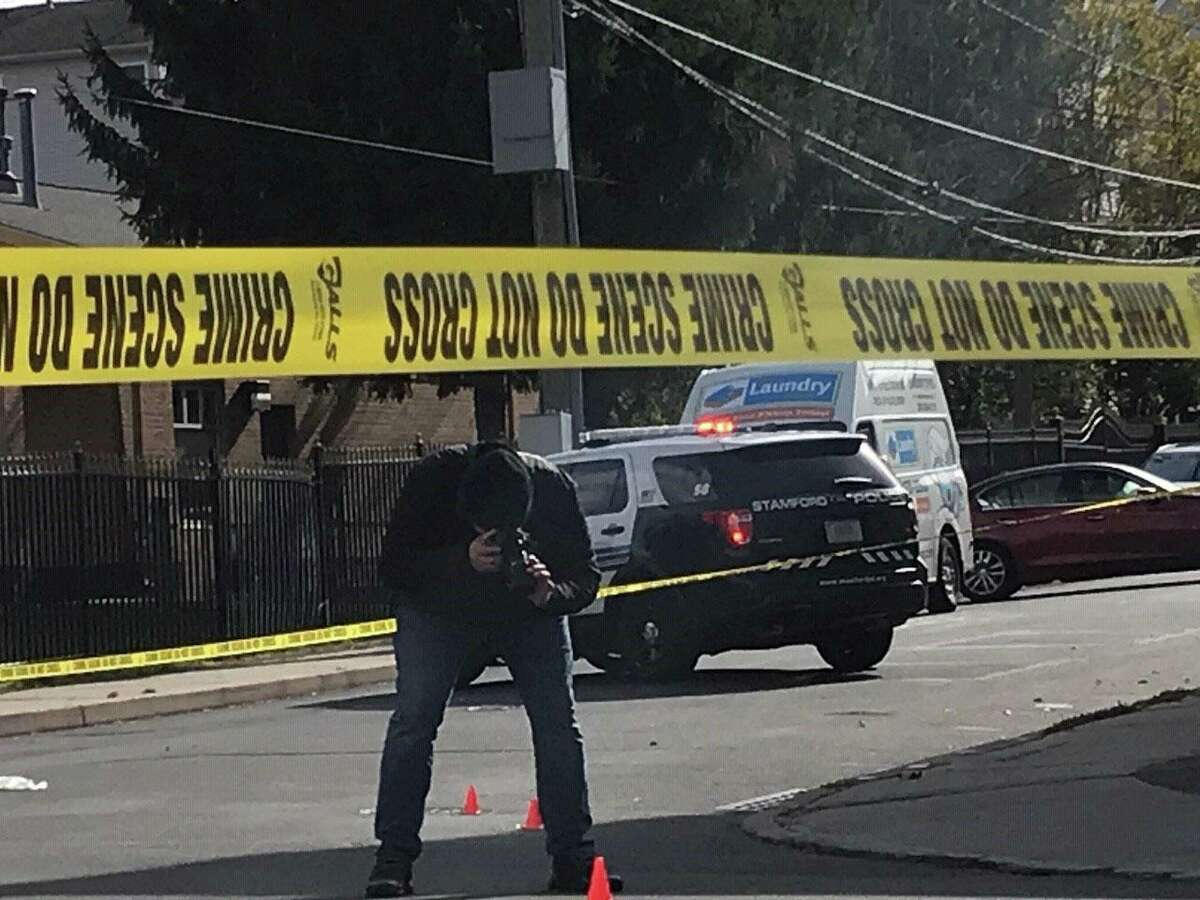 Crime scene investigators document and collect four shell casings at a noon shooting, where one man fired on another at Stillwater Avenue and Virgil Street in Stamford on Tuesday, Nov. 3.
