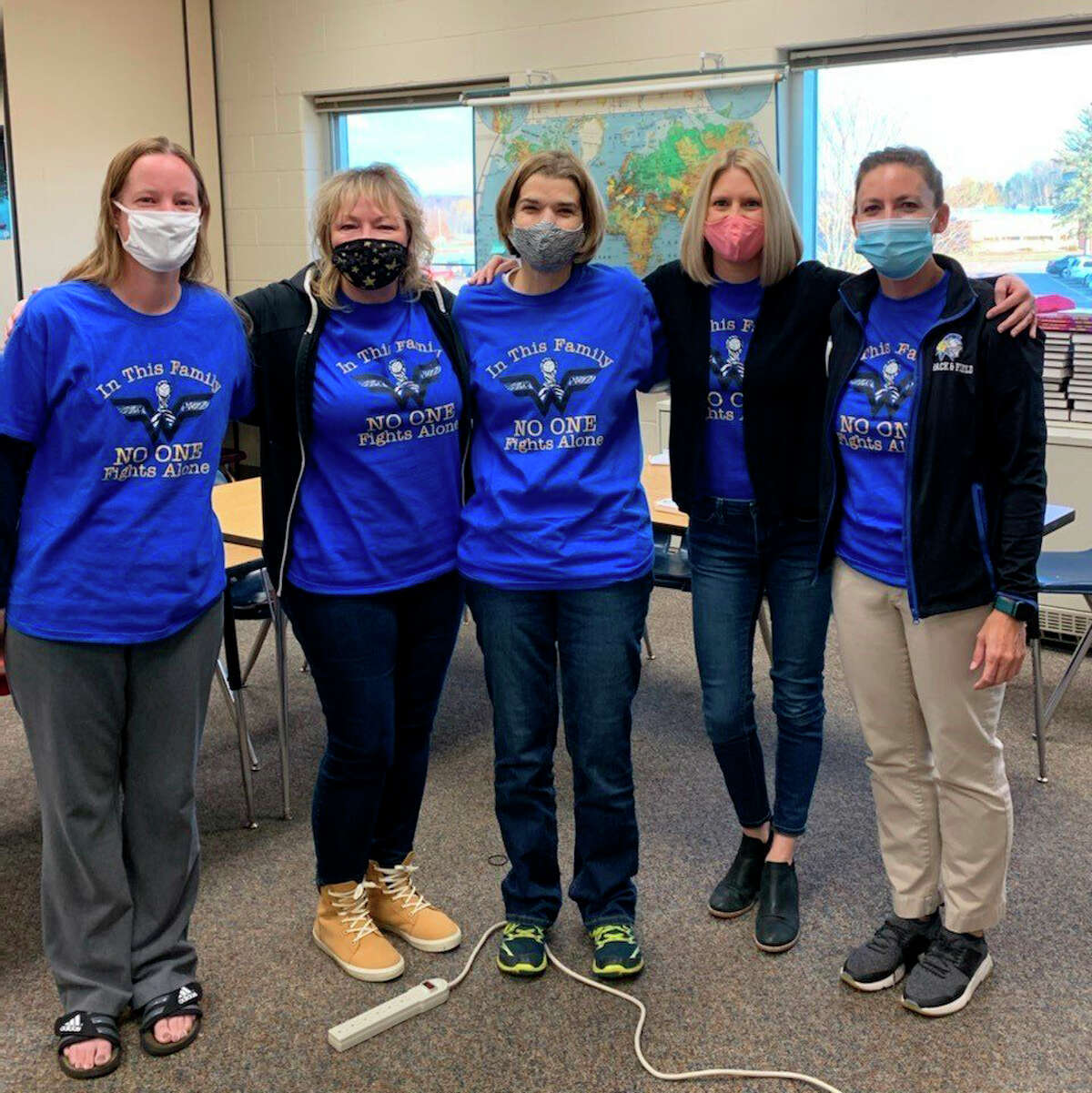 Michelle Howarth (center) stands with the Morley Stanwood sixth-grade team. The school hosted the Whipple Warrior Fundraiser to offset the cost of Howarth's medical expenses.