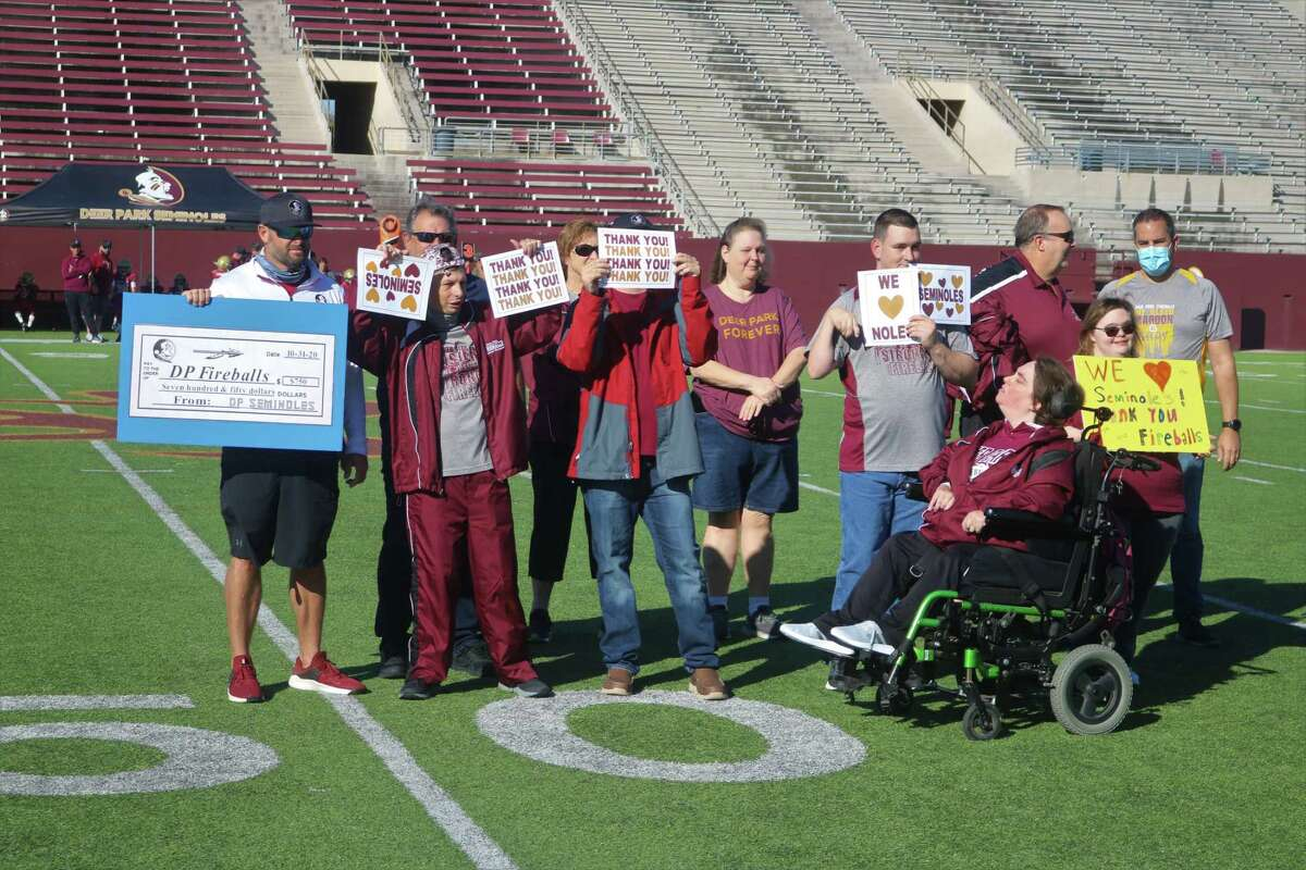 Seminoles representative Dax Kiefer (far left) holds up a check for $750 that he presented to the Deer Park Fireballs during halftime ceremonies of the Seminoles Freshmen game this past Saturday.