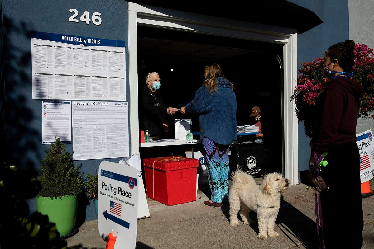 From left: Gerry Audet hands out a sticker to Liz Rahner after she dropped off her ballot at the Election Day polling place inside the garage at 246 Bocana St., Tuesday, Nov. 3, 2020, in San Francisco, Calif. Rahner's friend Juan Pablo Mendoza and his dog Bobi Mendoza wait for her friend.