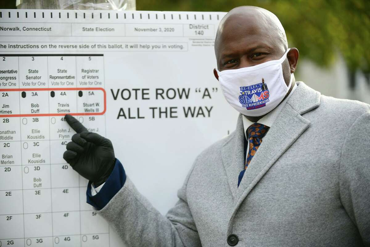 Travis Simms campaigns at the polling station at Columbus Magnet School in Norwalk on Tuesday.