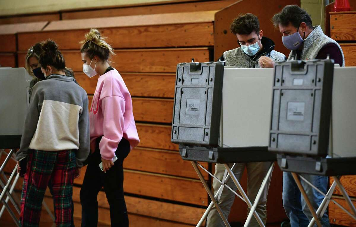 Voters including memebers of the Hingtgen family cast their ballots at the polling station at Roton Middle School Tuesday, November 2, 20202, in Norwalk Conn.