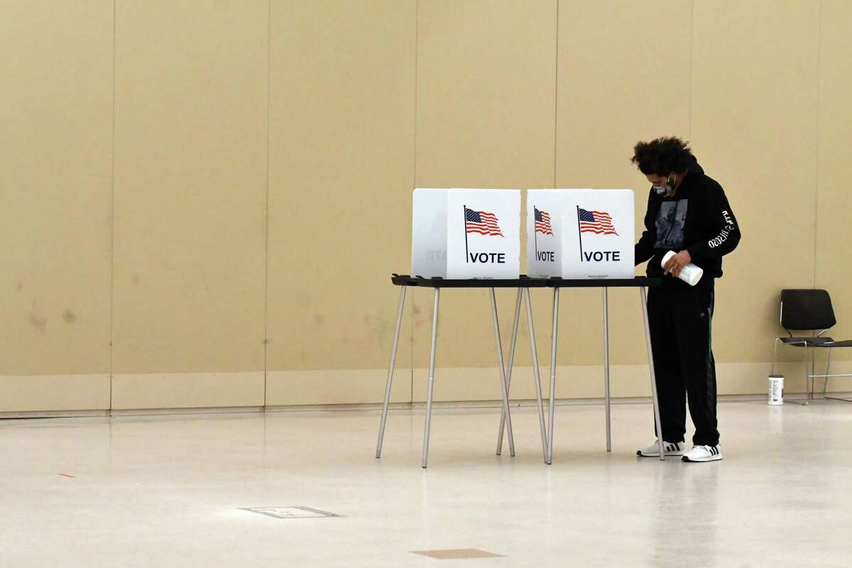 Volunteer poll worker James Clay disinfects voting booths at the Saratoga Springs City Center polling station on Tuesday, Nov. 3, 2020, on Broadway in Saratoga Springs, N.Y. (Will Waldron/Times Union)