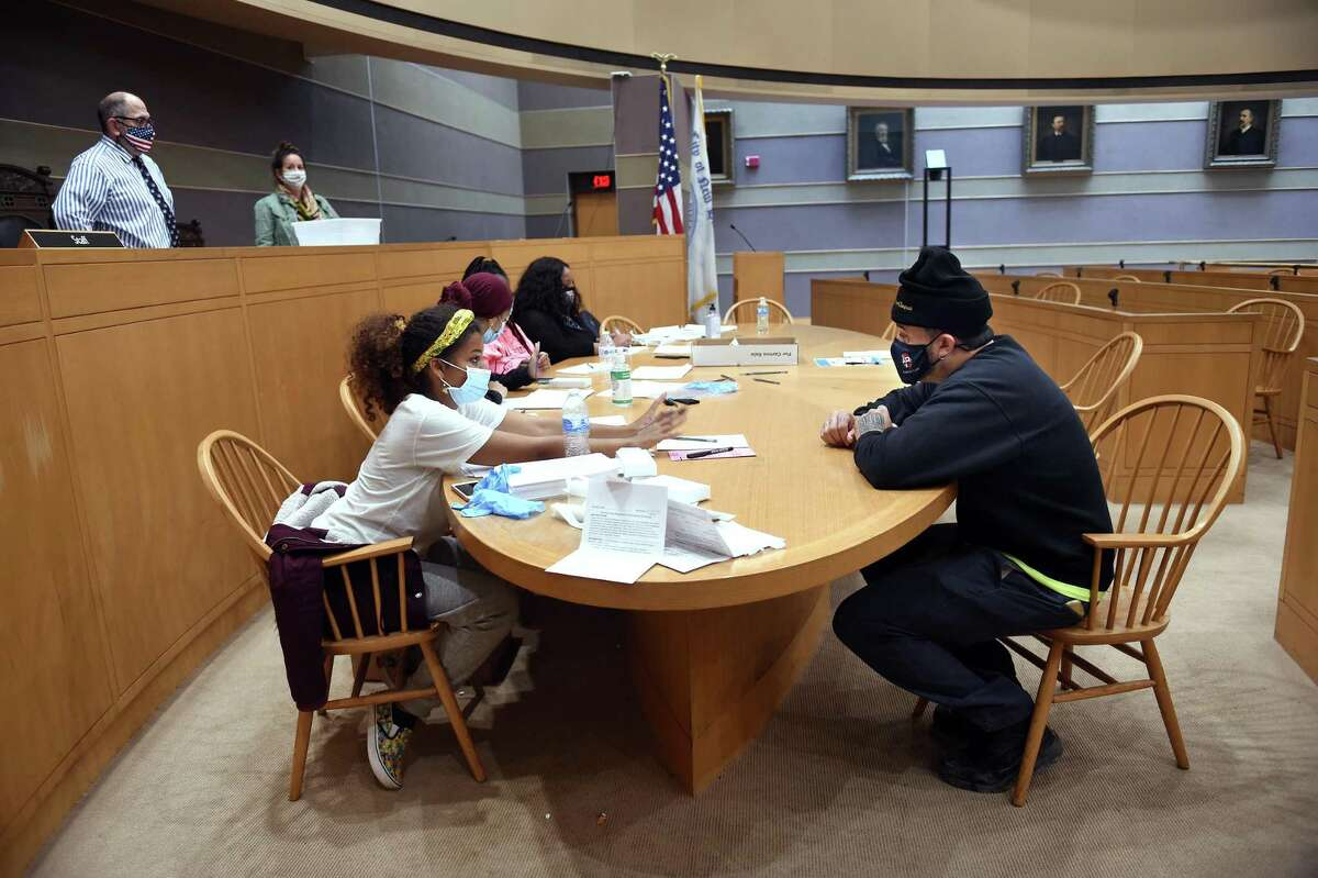 Ballot clerk Rianne Mustafa, seated at left, hands Jose Rodriguez, right, of New Haven a ballot in the Aldermanic Chambers at City Hall in New Haven on Tuesday. Rodriguez said he registered and voted on Election Day.