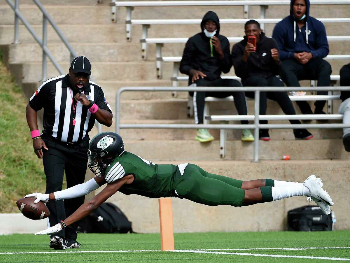 Hightower wide receiver Caleb Douglass, bottom, dives in to the end zone for a touchdown during the second half of a high school football game against Foster, Saturday, Oct. 24, 2020, in Sugar Land, TX.