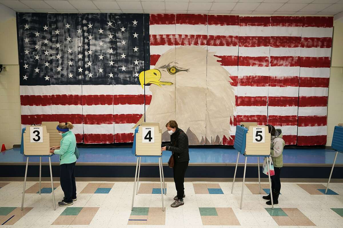 Voters cast their ballots under a giant mural at Robious Elementary school on Election Day, in Midlothian, Va., Tuesday Nov. 3, 2020. Poll workers said that traffic was slow due to all the early voting in the precinct. (AP Photo/Steve Helber)