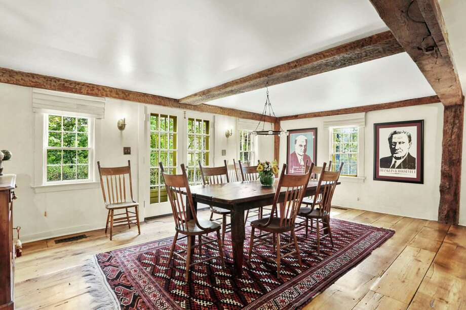 The formal dining room features wide-planked chestnut wood flooring, exposed posts and beams, and the current owners have on display large posters of Presidents Herbert Hoover and Franklin D. Roosevelt. This house actually pre-dates the official founding of America. This slate blue house with its distinctive red front door was built in 1700, making the John Platt House one of the oldest in Westport. Over the past centuries this house underwent renovations, updating and an expansion, which pushed the square footage to just over 4,000 feet, distributed through 11 rooms. The iconic historical landmark received a plaque in 1985 from then-Connecticut Governor William O'Neill honoring it as the oldest house in Westport during the state's 350th birthday. It was later learned that there was a house on Long Lots Road that is older still. The noteworthy structure has been included on two Westport Historical Society house tours, one in 2007 and the other in 2016.  Photo: Contributed Photo /