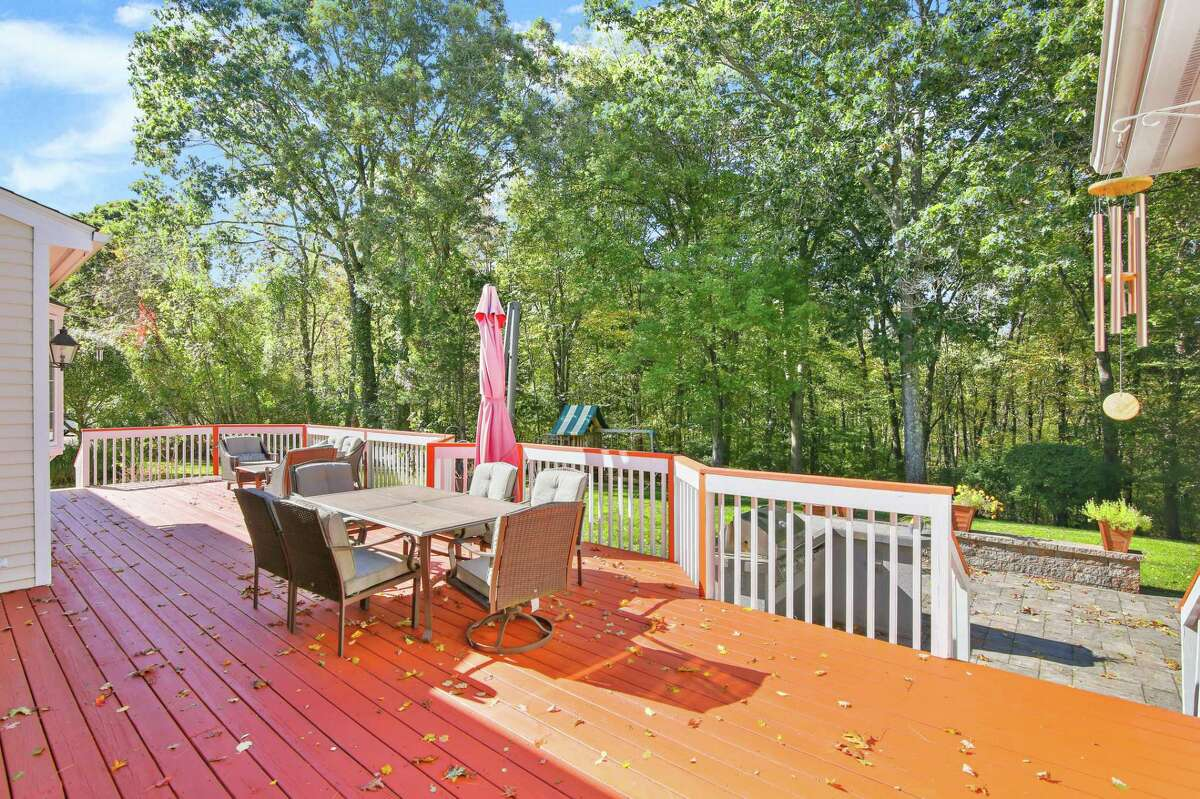 The sizable raised wood deck looks over this home's 3.49-acre level property.