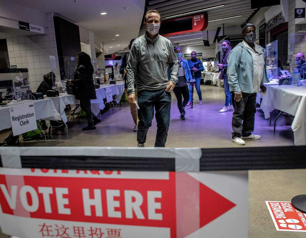 Washington Wizards Coach Scott Brooks walks his ballot through the process on Election Day at Capital One Arena with players from the Wizards and the WNBA's Washington Mystics.