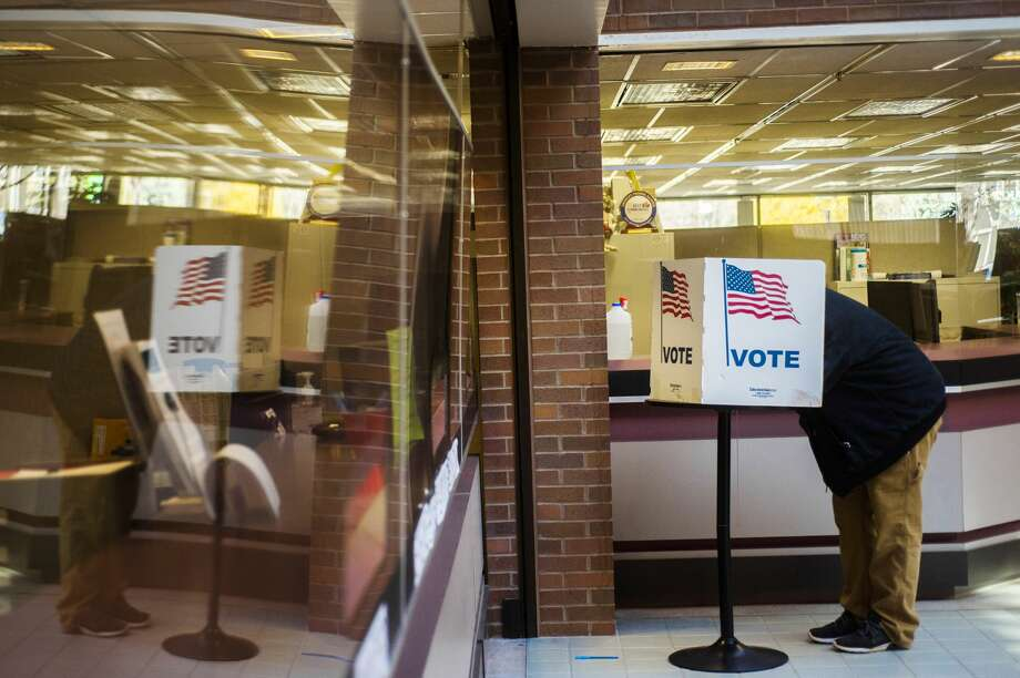 A voter is reflected in a plexiglass shield as they fill out their ballot at City Hall Tuesday, Nov. 3, 2020 in Midland. (Katy Kildee/kkildee@mdn.net) Photo: (Katy Kildee/kkildee@mdn.net)