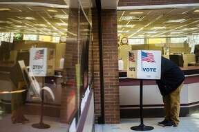 A voter is reflected in a plexiglass shield as they fill out their ballot at City Hall Tuesday, Nov. 3, 2020 in Midland. (Katy Kildee/kkildee@mdn.net)