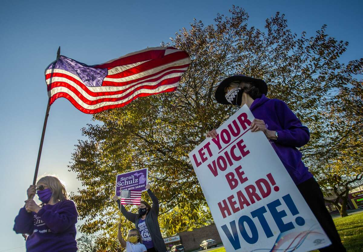 Volunteers and supporters of Sarah Schulz's campaign hold one of several rallies across town Tuesday, Nov. 3, 2020 at the corner of Ashman Street and Saginaw Road. (Katy Kildee/kkildee@mdn.net)