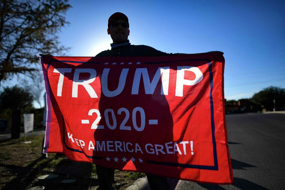 A supporter of Republican incumbent Donald J. Trump works the streets for votes at the Mission Branch Library polling place on election day, Tuesday, Nov. 3, 2020.