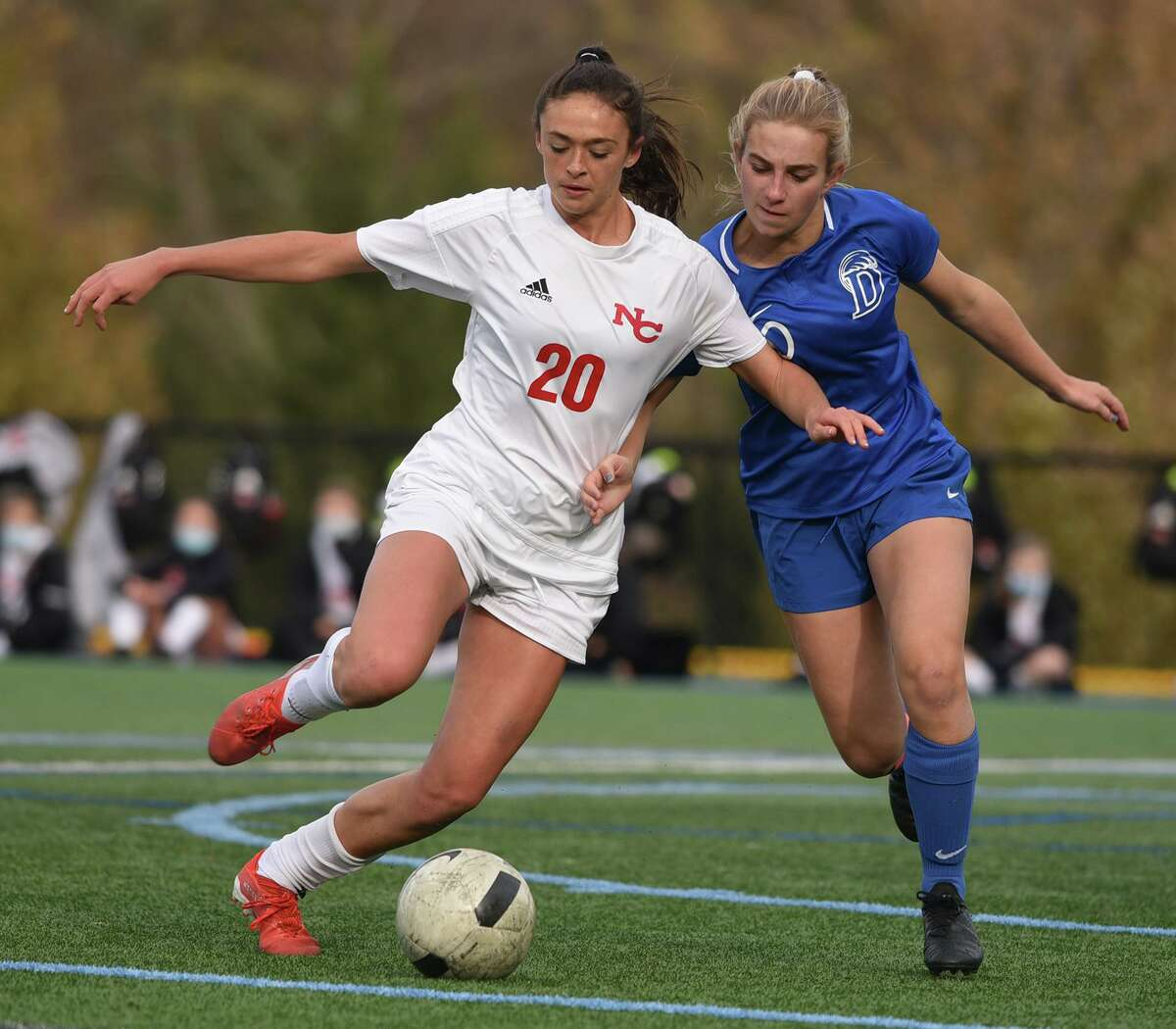 New Canaan's Emma Schuh (20) and Darien's Nelle Kniffin battle for the ball on Tuesday.