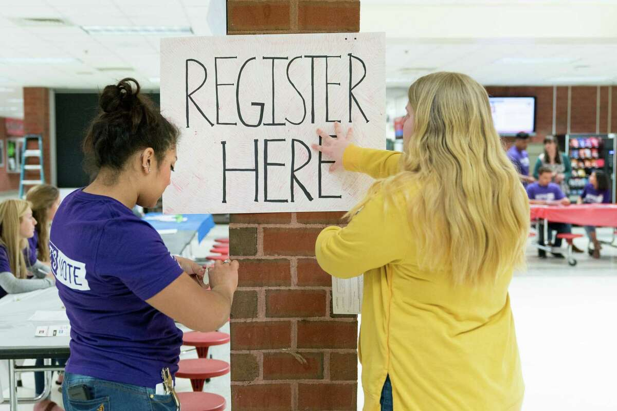 FILE -- Student volunteers post a voter registration sign for a student voter registration event at Brooke Point High School in Stafford, Va., April 12, 2018. Fewer than half of Americans 18 to 29 voted in the 2016 presidential election - a gap of more than 15 points compared with the overall turnout. (Erin Schaff/The New York Times)