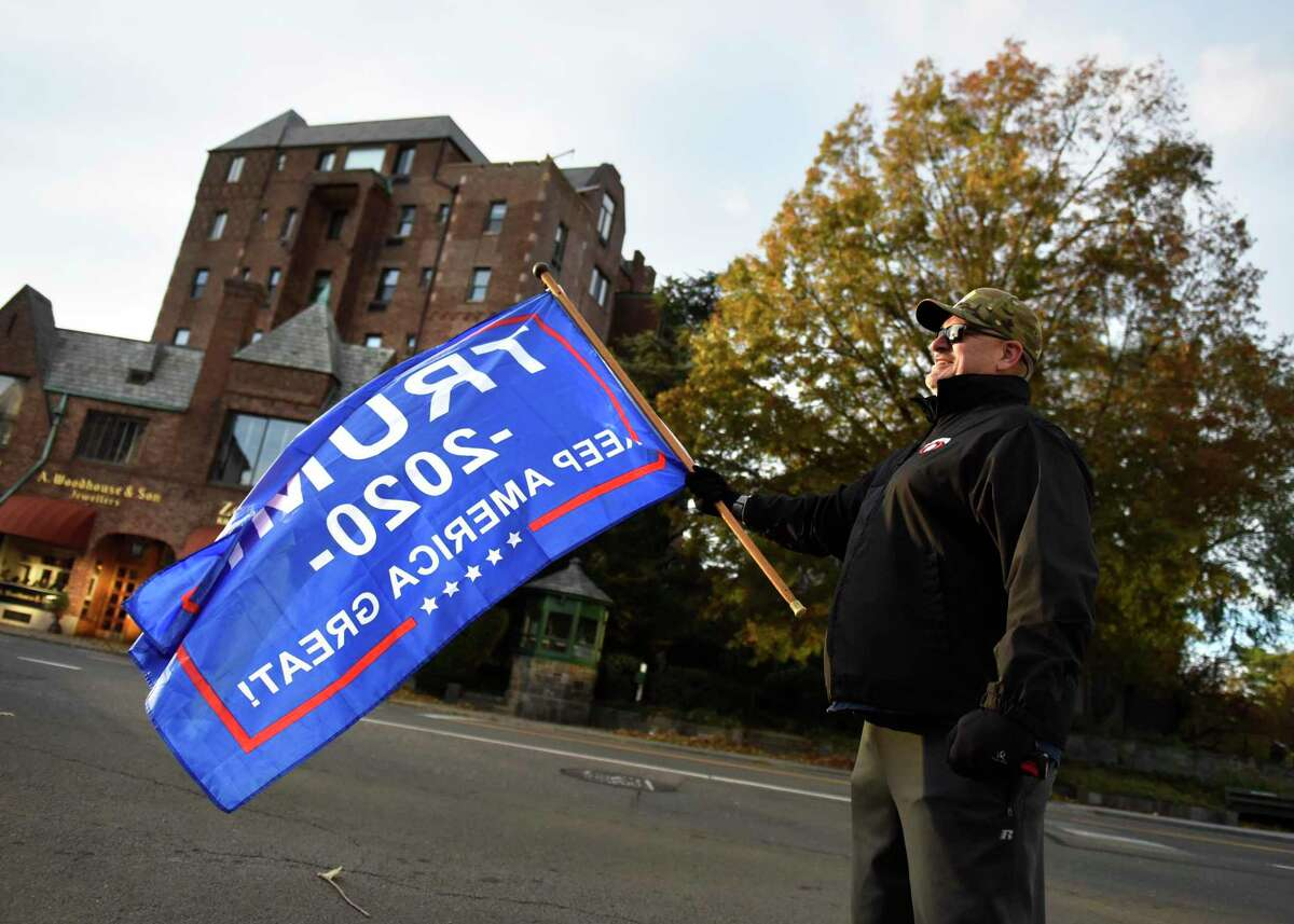 Greenwich's Christopher Jay, an Iraq War combat veteran, waves a Trump flag on Election Day 2020 at the top of Greenwich Avenue in Greenwich, Conn. Tuesday, Nov. 3, 2020. Connecticut residents cast their votes Tuesday in the Presidential Election between incumbent Republican Donald Trump and Democratic challenger Joe Biden.
