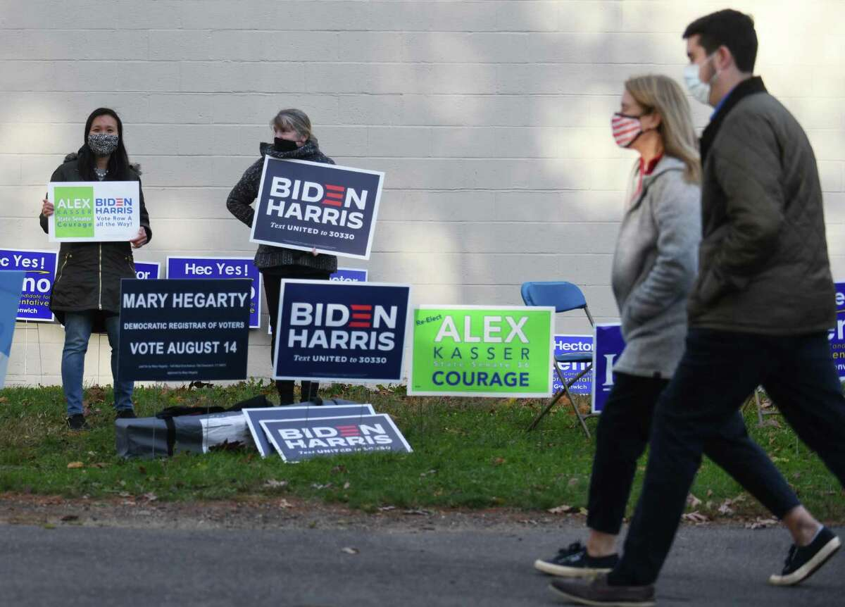 Cos Cob residents Janet McMahon, left, and Sheila Phelan hold signs supporting Democratic candidates on Election Day 2020 outside the District 8 polling center at Central Middle School in Greenwich, Conn. Tuesday, Nov. 3, 2020. Connecticut residents cast their votes Tuesday in the Presidential Election between incumbent Republican Donald Trump and Democratic challenger Joe Biden.
