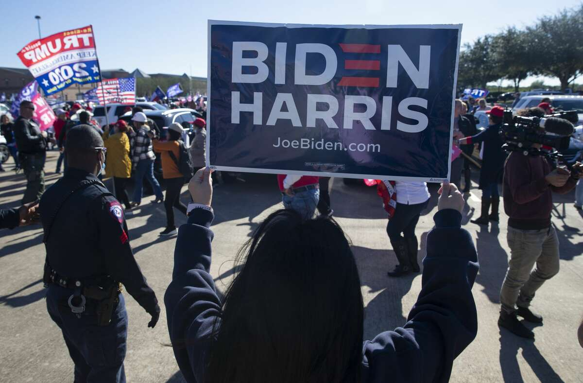 A Biden supporter holds up a campaign sign at the
