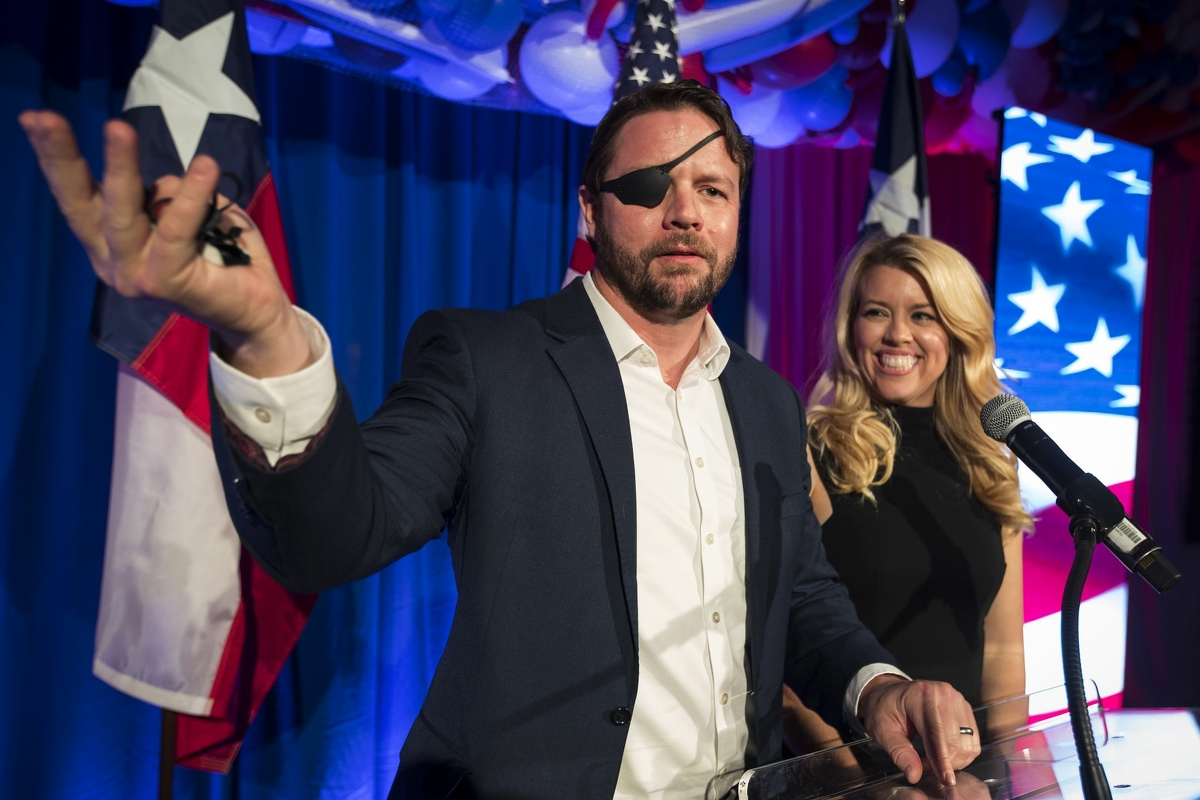 Rep. Dan Crenshaw, R-Texas, stands with his wife, Tara, as he welcomes his supporters to an election night watch party Tuesday, Nov. 3, 2020 in Houston.