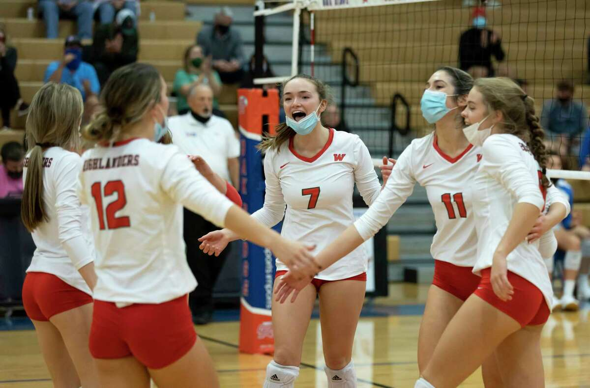 The Woodlands volleyball players react after winning the fourth set of a District 13-6A volleyball match at Oak Ridge High School in Oak Ridge North.