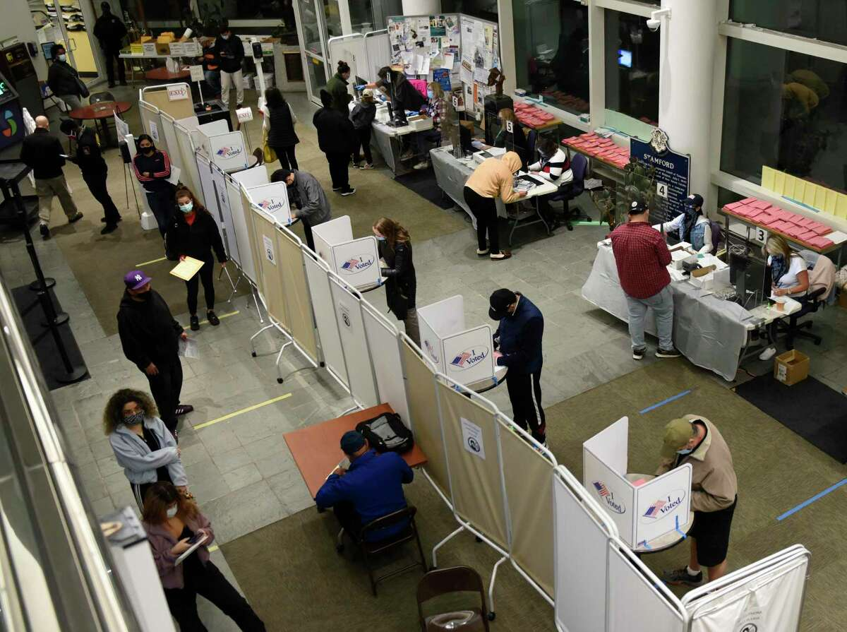 Stamford residents wait in line for same day voter registration and cast their ballots at the Government Center in Stamford, Conn. Tuesday, Nov. 3, 2020.