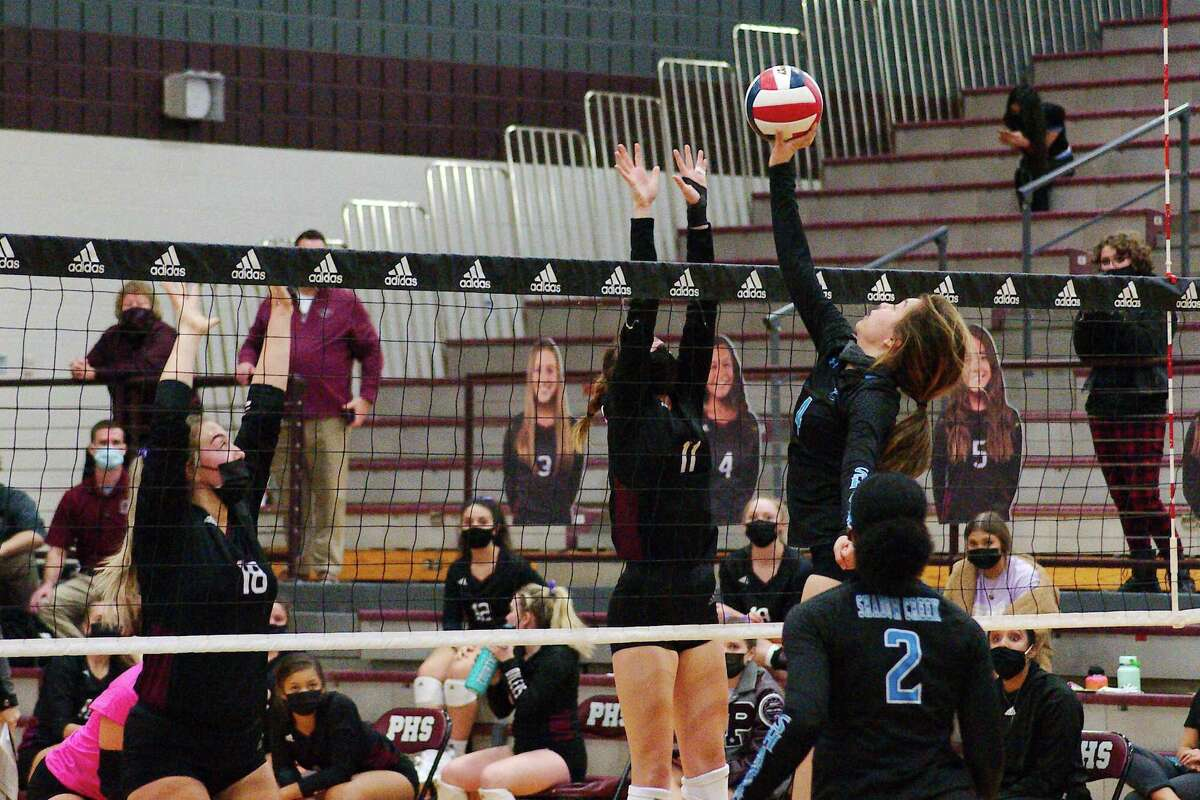Shadow Creek's Michele Murphy (4) tries to tip the ball over Pearland's Abbygail Thoren (11) Tuesday at Pearland High School.